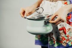 Ama de casa que cocina con el cazo imagen de archivo