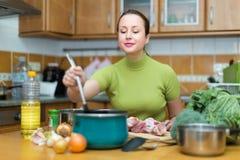 Ama de casa que cocina en la cocina imágenes de archivo libres de regalías
