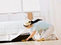 Ama de casa que extrae el zapato de debajo cama foto de archivo libre de regalías