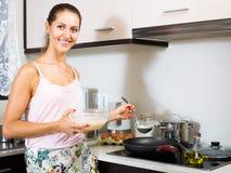 Ama de casa que fríe la tortilla foto de archivo