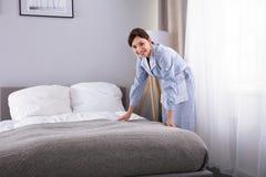 Ama de casa que hace la cama en la habitaci?n foto de archivo