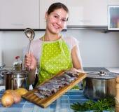 Ama de casa que intenta la nueva receta del sprattus en cocina Foto de archivo