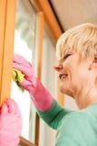 Ama de casa que limpia sus ventanas en los guantes de goma Imagenes de archivo
