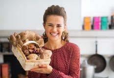 Ama de casa que muestra la cesta con las setas Imagen de archivo libre de regalías