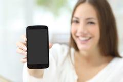 Ama de casa que muestra una pantalla en blanco del teléfono Imágenes de archivo libres de regalías
