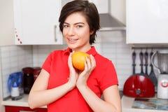 Ama de casa que se considera anaranjada en cocina imagen de archivo