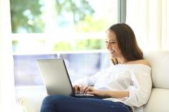 Ama de casa que usa un ordenador portátil que se sienta en el sofá Fotografía de archivo libre de regalías