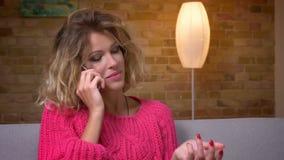 Ama de casa rubia del tiro del primer en suéter rosado en el sofá que habla emocionalmente en smartphone en atmósfera casera acog metrajes