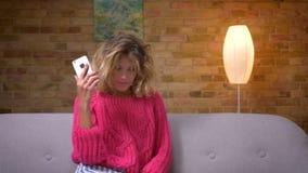 Ama de casa rubia en el suéter rosado que elige la posición para hacer selfies en smartphone en atmósfera casera acogedora almacen de video