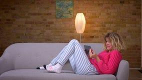 Ama de casa rubia en el suéter rosado que miente en el sofá que habla en videochat en la tableta en atmósfera casera acogedora almacen de video