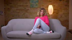Ama de casa rubia en suéter rosado en programas que cambian del sofá sobre la TV con el control remoto en el hogar acogedor almacen de video