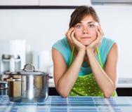 Ama de casa triste que cocina la cena Imágenes de archivo libres de regalías