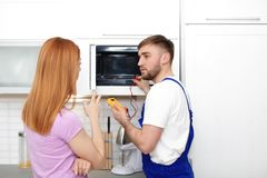 Ama de casa y reparador cerca del horno de microondas fotos de archivo