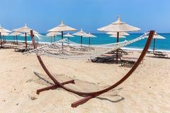 Amaca con gli ombrelli di spiaggia alla costa Fotografia Stock Libera da Diritti