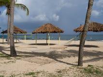 Amaca, Tiki Huts e rete di pallavolo sulla spiaggia fotografia stock libera da diritti