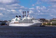 Amacie a opinião do tamanho do envelope da borda do navio colorido grande branco do oceano no rio de Neva de St Petersburg sob o  Imagens de Stock