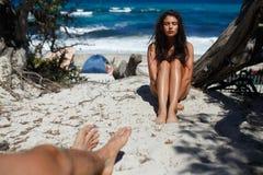 Amado hace toca a su novia Amor en el concepto del aire, asunto en la playa de la isla de Córcega foto de archivo