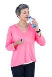 Amadureça a água potável da mulher quando música de escuta Fotos de Stock