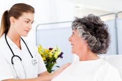 Amadureça a mulher que fala com sua enfermeira imagem de stock