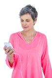 Amadureça a mulher que usa o telefone celular quando música de escuta Imagens de Stock