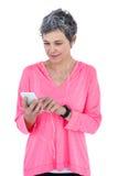 Amadureça a mulher que usa o telefone celular quando música de escuta Imagens de Stock Royalty Free