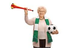 Amadureça o fã de futebol fêmea com uma trombeta e um futebol fotografia de stock royalty free