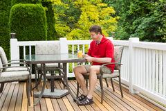 Amadureça o homem que aprecia o suco de laranja ao preparar-se para ler exterior Imagens de Stock Royalty Free