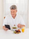 Amadureça o livro de leitura do homem ao comer o café da manhã Fotografia de Stock Royalty Free