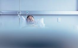 Amadureça o paciente masculino doente que dorme na cama de hospital imagens de stock royalty free