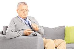 Amadureça-se assentado em um nível de medição do açúcar do sofá no sangue usando o glu Fotografia de Stock
