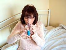 Amadureça a senhora atrativa que senta-se em sua cama usando o dispositivo asmático do espaçador da bomba para facilitar a circun imagens de stock