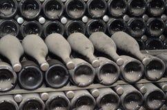 Amadurecimento em umas garrafas empoeiradas do champanhe na adega das adegas de vinho Fotografia de Stock
