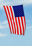 The Amaerican Flag waves in the wind on a blue sky background Royalty Free Stock Image