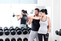 Amaestrador personal de la mujer de la gimnasia con el entrenamiento del peso imagen de archivo
