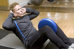 Amaestrador personal que hace ejercicios abdominales Imagen de archivo libre de regalías
