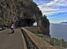 A couple on motorbike traveling along the scenic Amalfi Coast Drive. Amalfi Coast, Italy - July 23, 2018: A couple motorbiking on a windy road along the famous royalty free stock photo