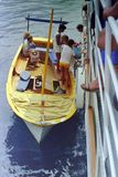 AMALFI, ITALIË, 1974 - een jonge zeeman helpt toeristen in het traditionele landen in Amalfi stock fotografie
