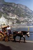 AMALFI, ITALY, 1992 - A patient horse pulls the wheelchair with two tourists on board and the coachman in the splendid panorama of stock photos