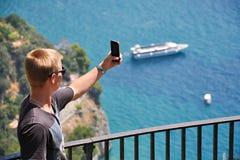 AMALFI-KÜSTE, ITALIEN - AUGUST, 8: Jugendlicher mit Smartphone über dem Meer, am 8. August 2013 Lizenzfreies Stockfoto
