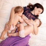 Amamantamiento de dos bebés gemelos de las pequeñas hermanas Fotos de archivo libres de regalías