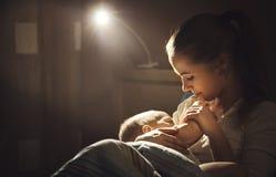 Amamantamiento mime al pecho de alimentación del bebé en noche de la oscuridad de la cama Imagenes de archivo