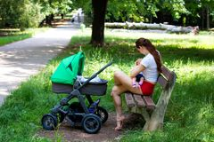 A amamentação infantil fora da cena, da jovem mulher atrativa e da mãe nova no mini short vermelho está mantendo o bebê e a nutri fotografia de stock