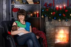 Amamentação nova da mãe e vista com amor em seu bebê perto da chaminé A parede atrás é decorada com bolas do Natal imagem de stock