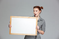 Amamzed cute woman holding and looking at blank whiteboard Stock Photos