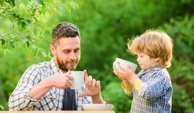 aman comer juntos El padre y el hijo del desayuno del fin de semana comen al aire libre Peque?o ni?o del muchacho con el pap? Ali fotos de archivo