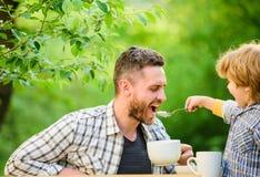 aman comer juntos Niño del muchacho del desayuno del fin de semana pequeño con el papá Comida org?nica y natural el padre y el hi fotografía de archivo