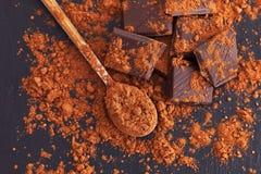 Łamana ciemna czekolada z kakaowym proszkiem zdjęcia royalty free