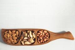 Amande, écrou brésilien et arachide dans une cuvette en bois Photographie stock libre de droits