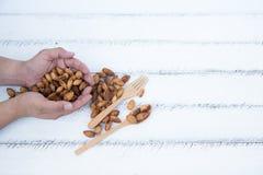 Amande, cuillère et fourchette sur la table en bois blanche Image stock