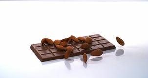 Amandelen die op melkchocolatablet vallen stock videobeelden